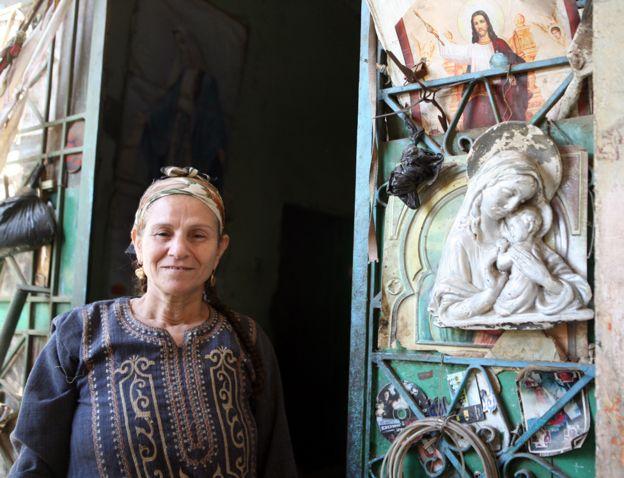 Mulher cristã posa em frente a sua casa