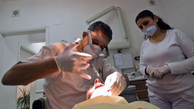 Una persona a la que el dentista le está inyectando anestesia