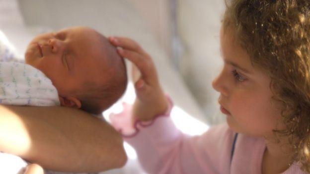 Criança faz carinho em bebê
