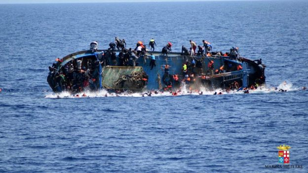 People try to jump in the water right before their boat overturns off the Libyan coast on 25 May