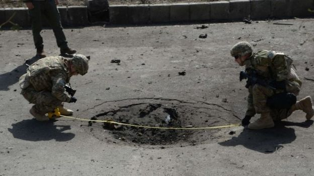 Nato soldiers measure a crater at the site of a suicide car bomb attack that targeted foreign military vehicles in Kabul (11 October 2015)