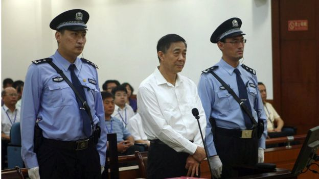 22 August 2013. Former Politburo member and Chongqing city party leader Bo Xilai, centre, on trial in eastern China's Shandong province. Standing flanked by security officers.