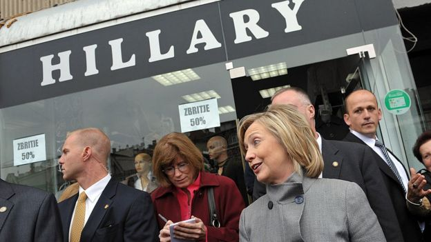 Then Secretary of State Hillary Clinton (C) smiles as she walks out of a store named in her honour in Pristina on 13 October 2010