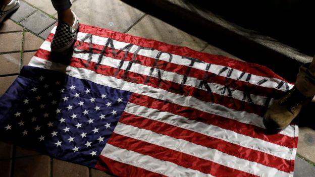 люди наступают на американский флаг