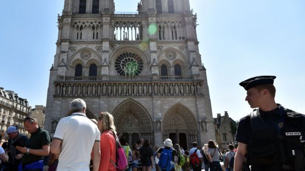 A French police officer stands guard by Notre Dame Cathedral in Paris as people queue for the mass for the feast of the Assumption on August 15, 2016.