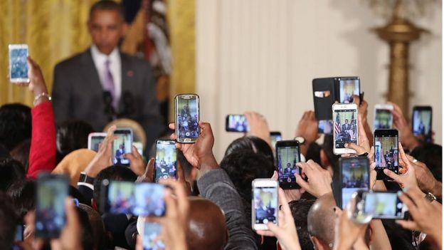 Decenas de celulares toman fotografías de Obama quien aparece en el fondo de manera borrosa.