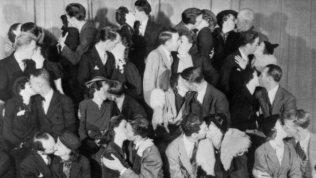 Foto en blanco y negro de muchas parejas besándose