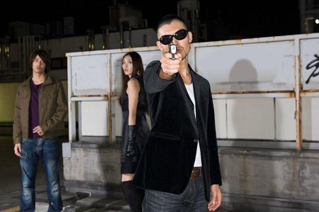 模特擺拍。 現在就連日本黑幫也很少用槍。