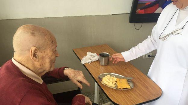 Un anciano frente a una mesa de comida