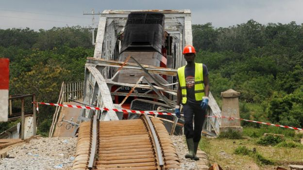 A worker walks next to a partially collapsed railroad bridge over the River Nzi, near Dimbokro, Ivory Coast - Thursday 8 September 2016