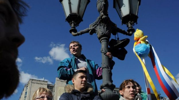 A woman holds up a yellow duck toy during protests in Moscow 26/03/2017