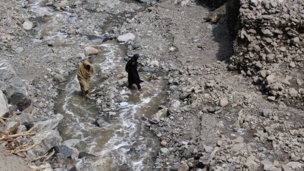 Women cross a stream after the road was destroyed during flash floods in Ursoon, a village near Chitral, on July 3, 2016.
