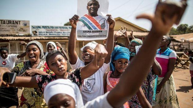 Personas festejan con un cartel de Adama Barrow.