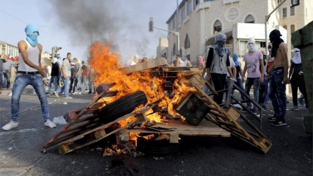 Masked Palestinians surround a bonfire in Shuafat, East Jerusalem (05/10/15)