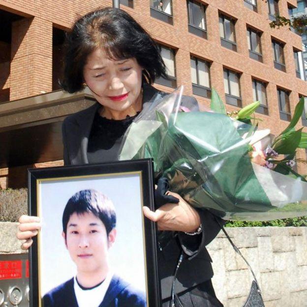 Fujie Sugiyama sostienen la foto de su hijo Takanori, declarado víctimas de karoshi en 2007