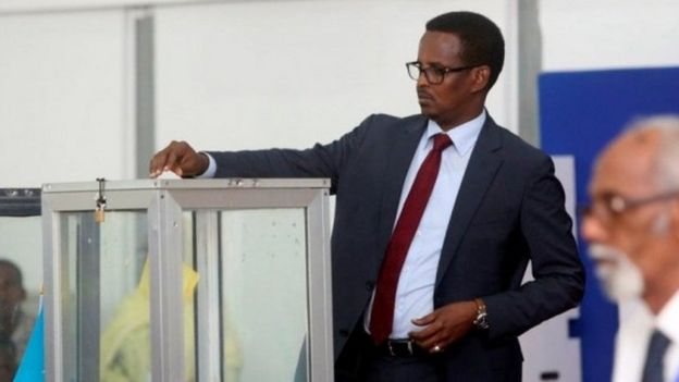 A Somali lawmaker casts his ballot during the presidential vote at the airport in Somalia