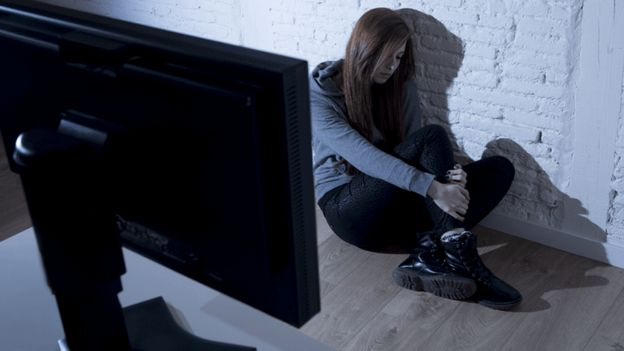 Woman hiding from laptop