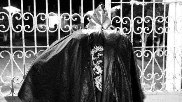 Animero frente a las puertas del cementerio.