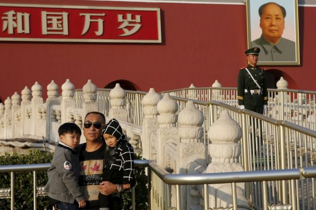 A man carrying his children in his arms poses for photograph in front of the giant portrait of late Chinese chairman Mao Zedong on the Tiananmen Gate in Beijing