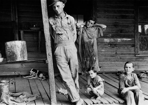 Uma família na varanda de sua casa durante a Grande Depressão