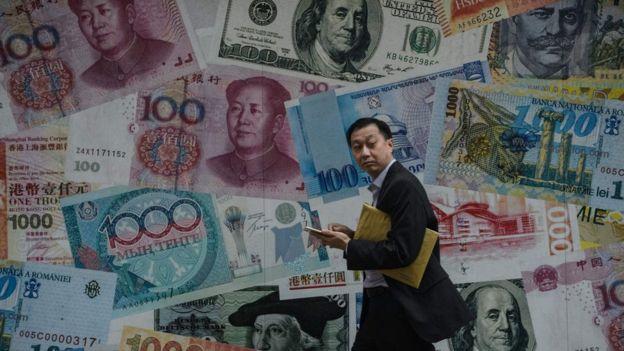 Hombre camina frente a un mural de billetes