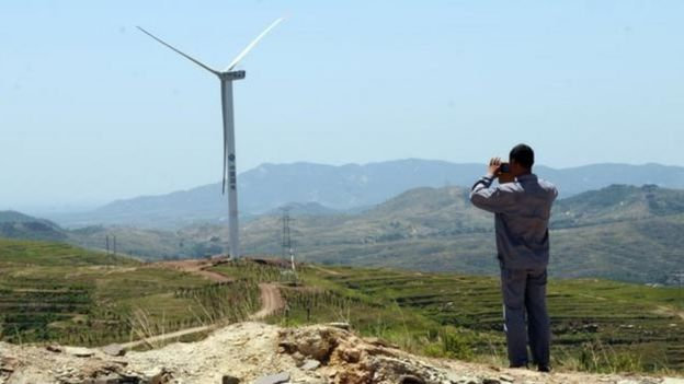 Un habitante de un poblado rural en China mira el horizonte con unos binoculares. Al fondo, un molino que produce electricidad por viento.