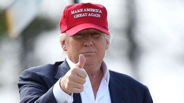 Donald Trump usa boné com mote da campanha e faz sinal de positivo em visita à Escócia em 2015