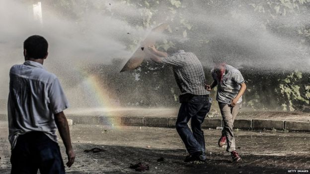 Left-wing militants take cover from a water cannon during clashes with Turkish police officers on 25 July
