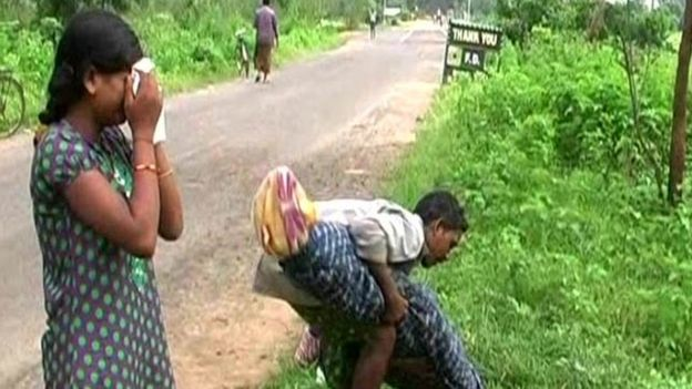 Man carries wife's body while his daughter weeps