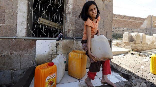 Uma menina iemenita tenta levar um bidão cheio de água limpa em uma fonte doados em meio a perturbações generalizadas em curso de abastecimento de água