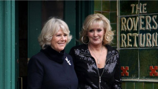 Camilla, Duchess of Cornwall laughs as she chats to cast member Beverley Callard outside the Rovers Return during a tour of the Coronation Street set on February 4, 2010