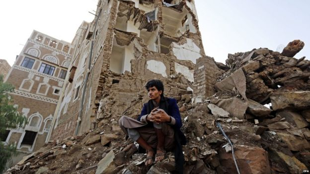 A Yemeni man looks on as a team of the International Committee of the Red Cross (ICRC) delegates inspects the scene of a Saudi-led coalition air strike in Sanaa's Old City (9 August 2015)