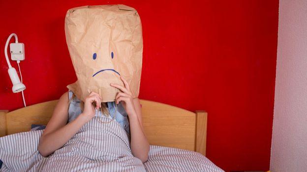 Mujer con una bolsa de papel en la cabeza.