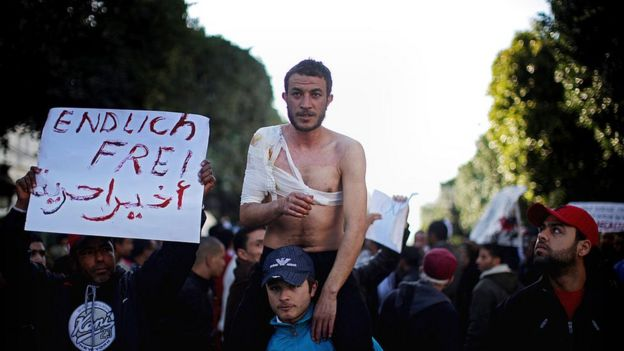 Injured protester being carried by another demonstrator in a crowd