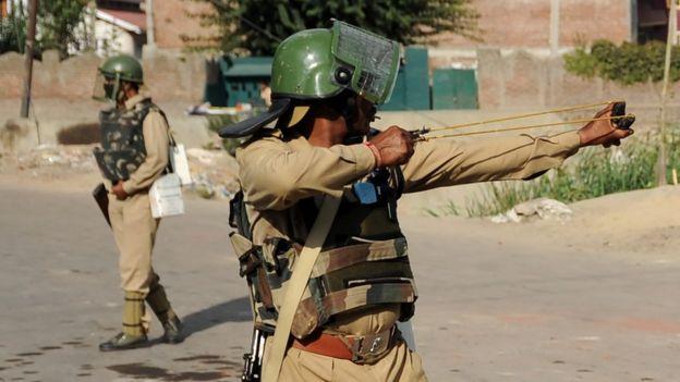 An Indian paramilitary officer aims a sling shot towards Kashmiri protestors during a clash in downtown Srinagar