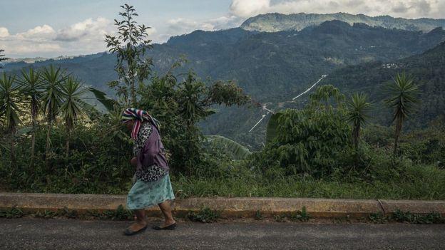 Una mujer camina sobre una vía cercana a la presa Aurora.
