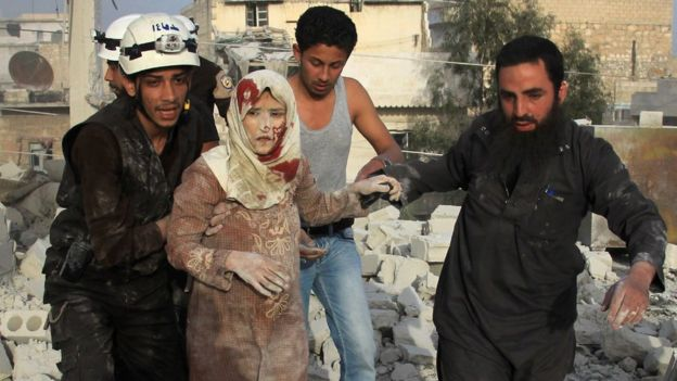 Syrian rescue workers and residents help an injured woman following a reported government air strike on the rebel-held Aleppo district of Haydariya. Photo: April 2016
