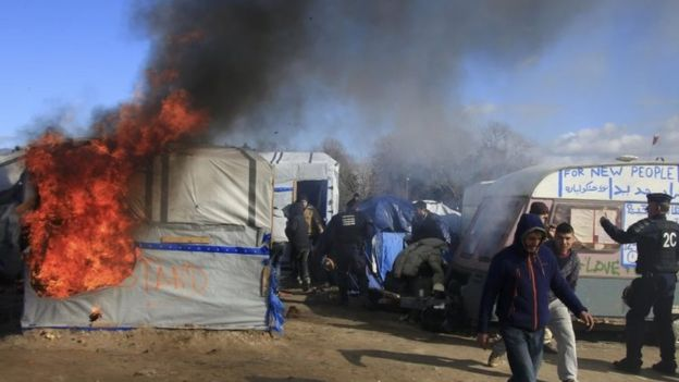 Smoke and flames rise from a burning hut in the Jungle camp in Calais