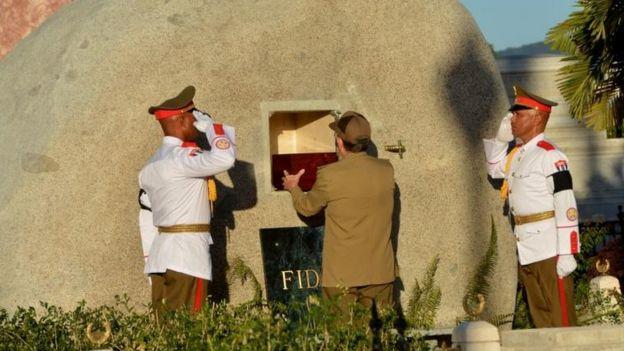 El presidente cubano, Raúl Castro, introduce la urna con las cenizas de Fidel en la piedra.