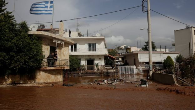 A Greek national flag flutters atop a terrace as locals observe a flooded street following heavy rainfall in the town of Mandra