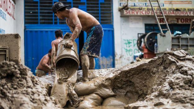 Hombre botando lodo de su propiedad, con ayuda de un balde.