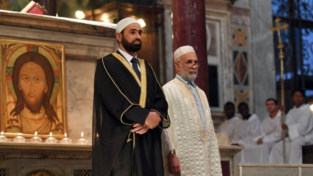 Iman Sami Salem (L) and Imam Mohammed ben Mohammed (R) stand during a mass in the church Santa Maria in trastevere in Rome on July 31, 2016