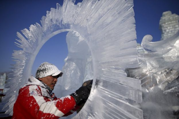 A worker polishes an ice sculpture