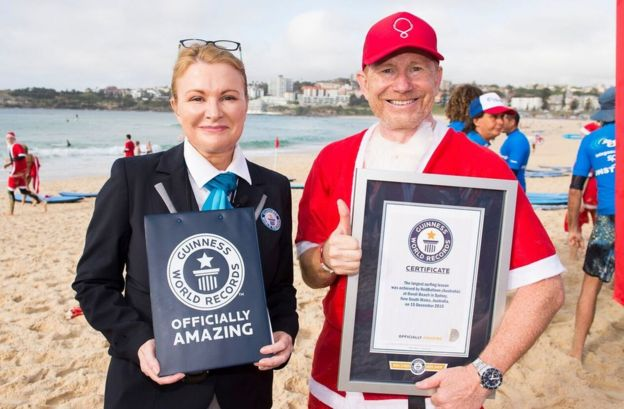 A pack of 320 surfing Santas embrace the Christmas spirit in Australia, breaking the Guinness World Record for the largest surf lesson