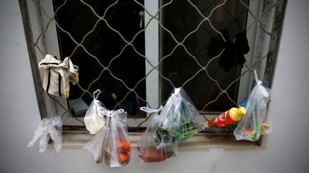 Zanahoria, queso y algunas legumbres cuelgan en bolsas plásticas de una ventana enrejada.