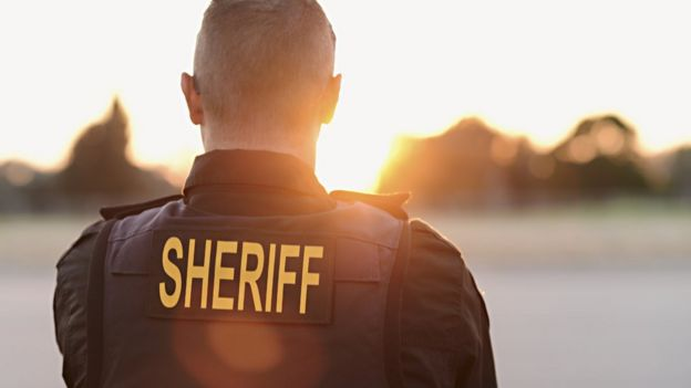 espalda de un hombre llevando un chaleco de Sheriff