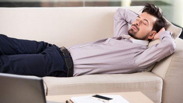Hombre de negocios duerme en un sofá.