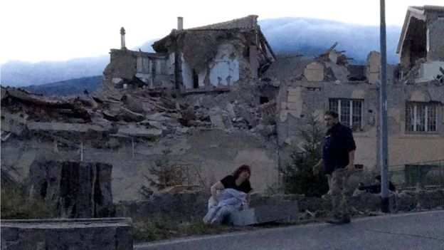 People stand by a road following a quake in Amatrice