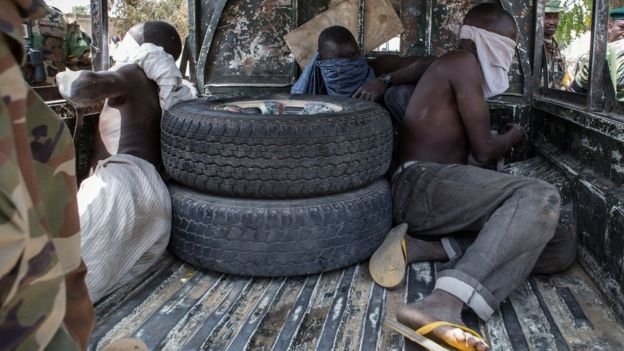 Three young men, who were discovered while entering Bama town, sit blindfolded in the back of a pick-up truck before being taken for interrogation by the Nigerian army on March 25, 2015.