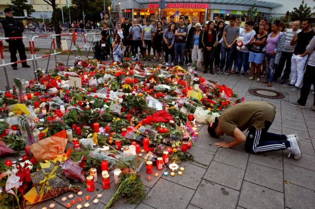 A man prays beside flowers laid in front of the Olympia shopping mall in Munich, Germany, 23 July